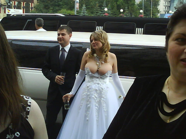 Wedding photobomb #7: This photo virtually redefines the very notion of a photobomb as the bride is essentially being photobombed by her own breasts – something we weren't sure was even possible.