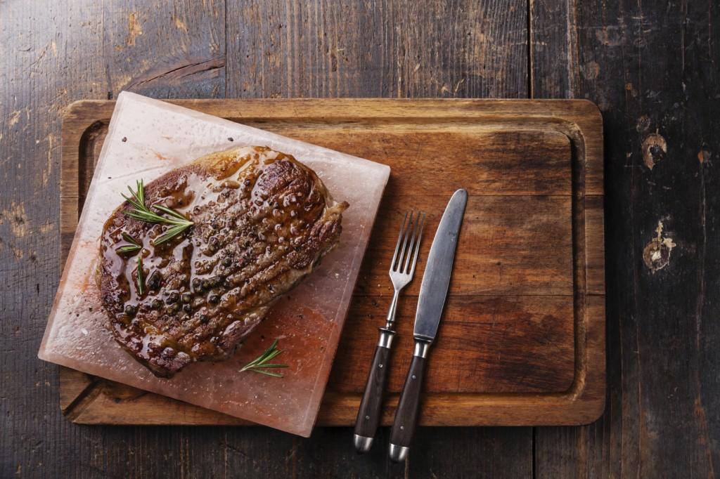 Grilled Black Angus Steak Ribeye on Himalayan pink salt block on dark wooden background
