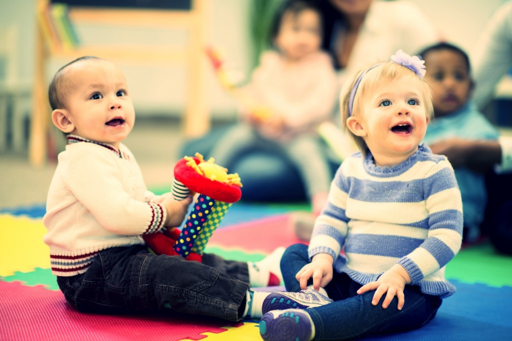 Small children (babies) laughing and playing together nicely in a daycare setting.