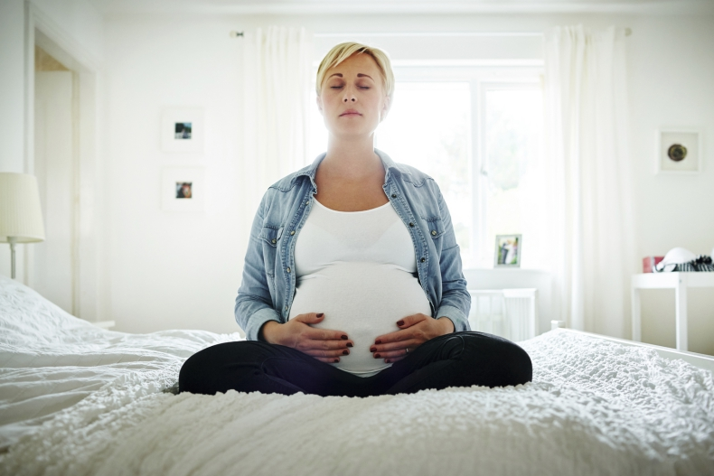 Pregnant woman meditating on her bed with her hands on her belly
