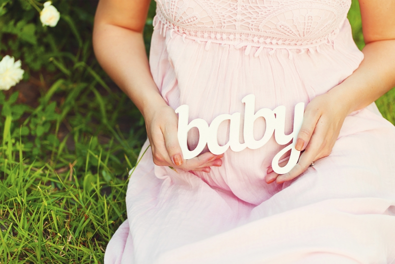 """Label """"Baby"""" in the hands of a pregnant woman outdoors"""