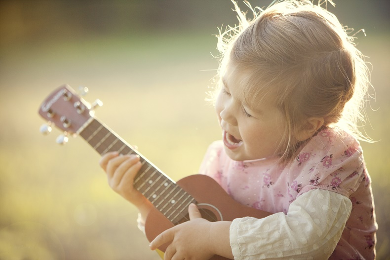 A young child playing a ukulele in the sunlight in a field