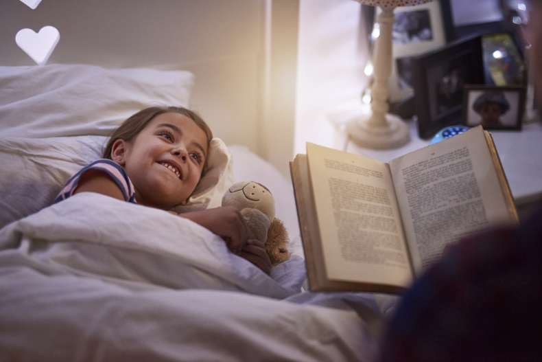 Shot of a father reading a bedtime story to his daughter