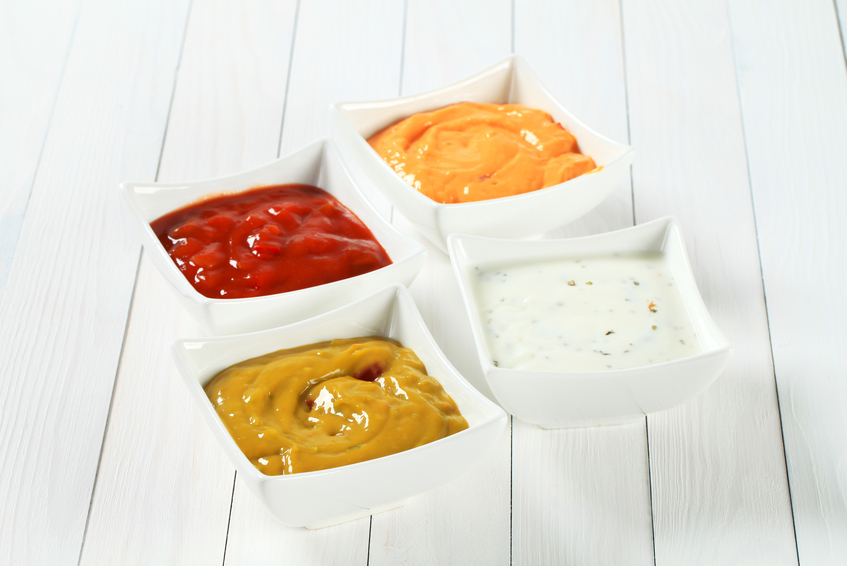 various salsa dips in white square bowls