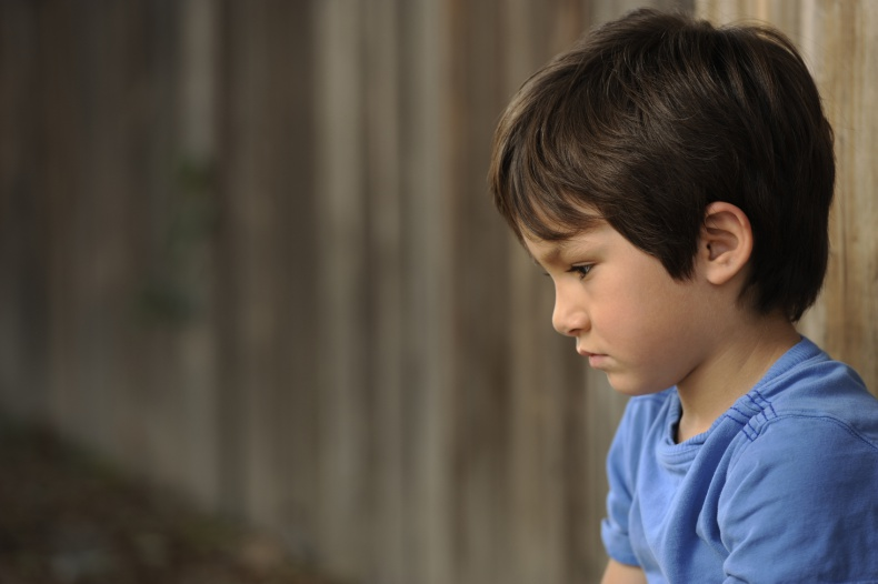upset boy leaning against a wooding fence