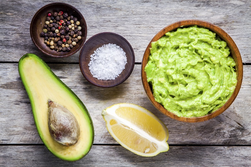 ingredients for homemade guacamole: avocado, lemon, salt and pepper