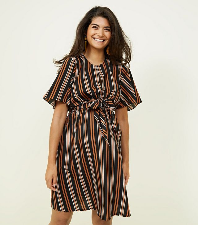 4281b8300816e The dress is from New Look's maternity section and it's got a vertical  orange and brown stripe, a tie front fastening, and a bump accommodating  design.